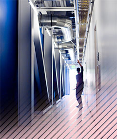 Silhouette of student posing in modern, light-filled, industrial corridor