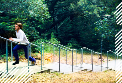 Student running up outdoor staircase on wooded campus