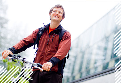 Smiling student with bicycle looking out on wooded campus